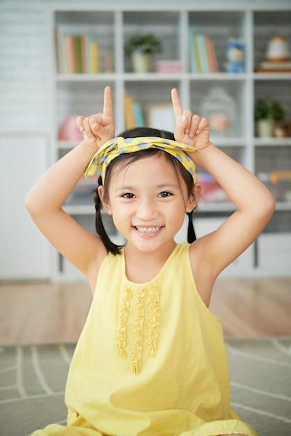 Sorridente menina chinesa sentado em casa e fazendo gesto de chifres de vaca Foto gratuita