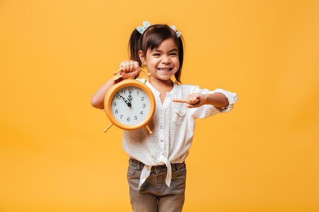 Sorridente menina segurando o relógio despertador. Foto gratuita