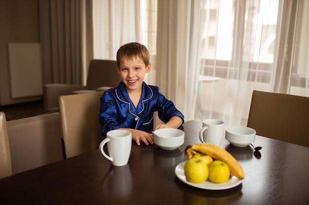 Sorridente menino senta-se à mesa de jantar e come alimentos saudáveis frutas e mingau Foto Premium