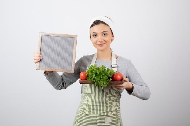 Sorridente modelo mulher bonita segurando uma placa de madeira com legumes frescos. Foto gratuita