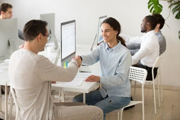 Sorridente mulher jovem handshaking satisfeito cliente fazendo negócio no escritório Foto gratuita