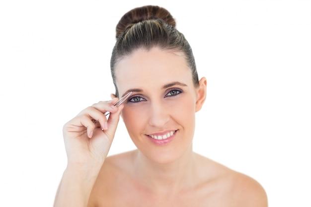 Sorridente mulher olhando câmera usando uma pinça Foto Premium