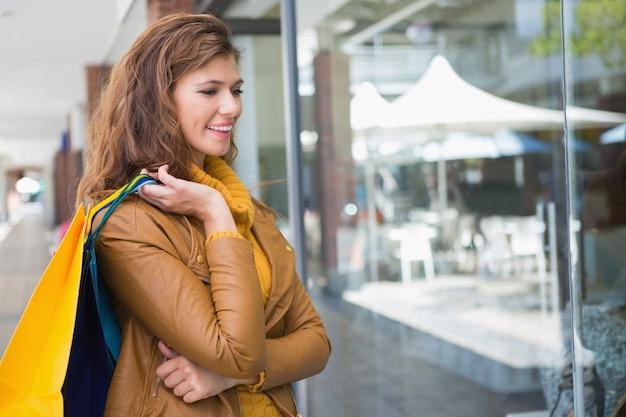 Sorridente, mulher, segurando, shopping, sacolas, olhar, janela Foto Premium