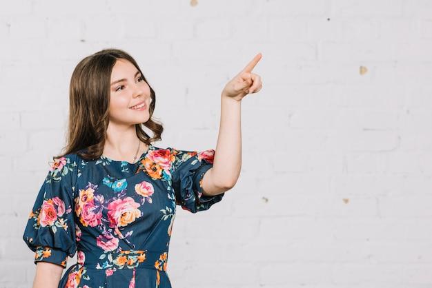 Sorrindo adolescente apontando o dedo para algo contra o pano de fundo Foto gratuita
