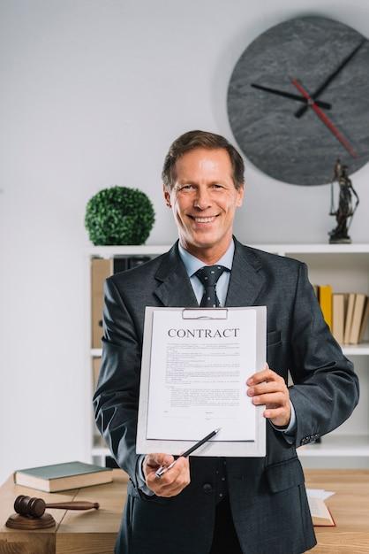 Sorrindo advogado maduro, apontando para o lugar de assinatura em um documento de contrato Foto gratuita