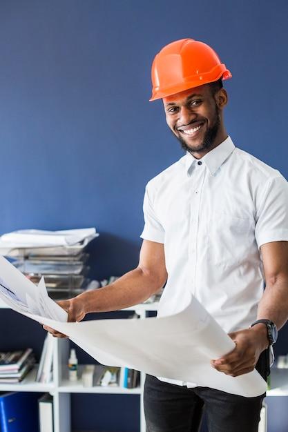 Sorrindo, africano, arquiteta, segurando, blueprint Foto gratuita