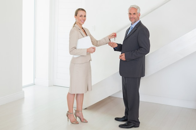Sorrindo, agente propriedade, entregar, teclas, para, cliente Foto Premium