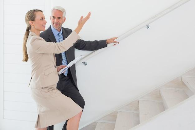 Sorrindo, agente propriedade, mostrando, escadas, para, comprador potencial Foto Premium