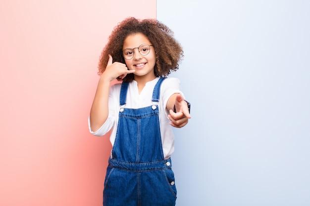 Sorrindo alegremente e apontando enquanto faz uma ligação, você gesticula mais tarde, falando no telefone Foto Premium