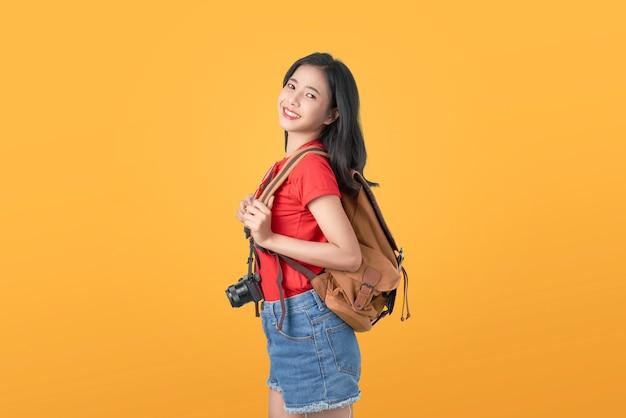 Sorrindo alegremente viajante de mulher asiática segurando a câmera e mochila Foto Premium