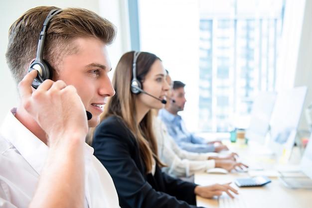 Sorrindo, amigável, homem, trabalhando, em, centro chamada, escritório, com, equipe Foto Premium
