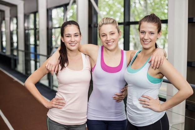 Sorrindo amigos atléticos abraçando na pista Foto Premium