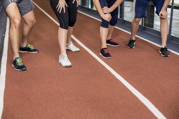 Sorrindo amigos atléticos vai começar a correr na pista Foto Premium
