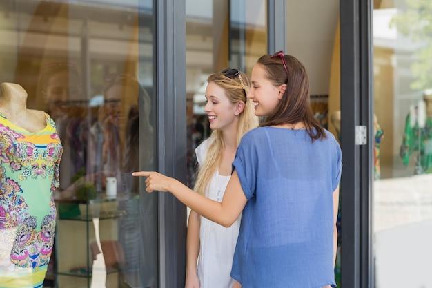 Sorrindo amigos dedo apontando um vestido Foto Premium