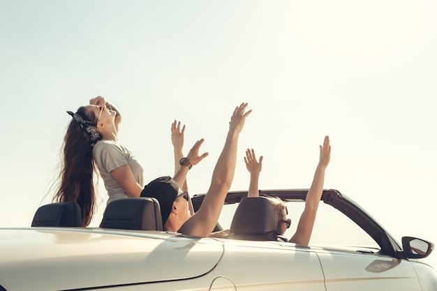 Sorrindo amigos dirigindo carro perto do mar e se divertindo Foto Premium