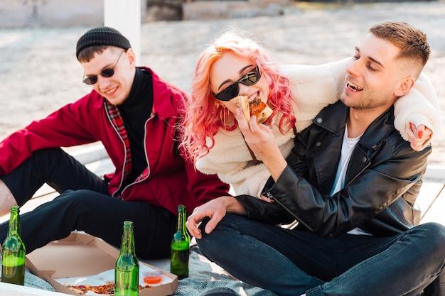 Sorrindo amigos se divertindo com cerveja e pizza ao ar livre Foto gratuita