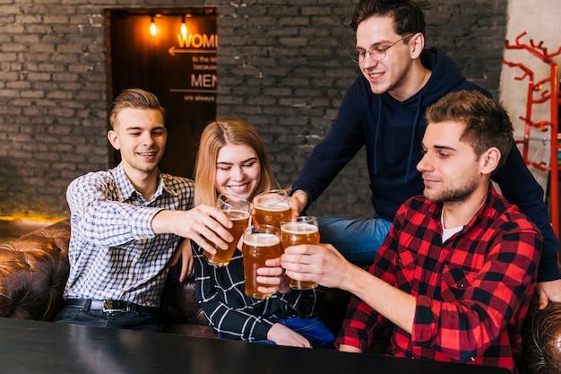 Sorrindo amigos sentados juntos, brindando os copos de cerveja Foto gratuita