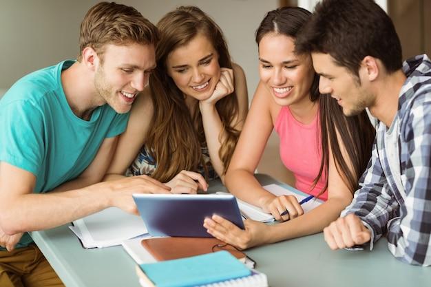 Sorrindo amigos sentados usando tablet pc Foto Premium