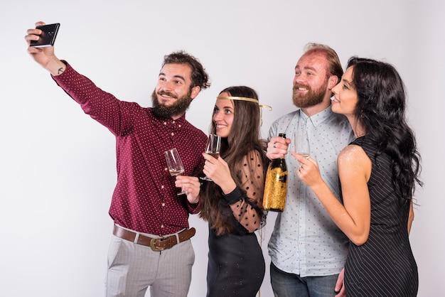 Sorrindo amigos tomando selfie na celebração Foto gratuita
