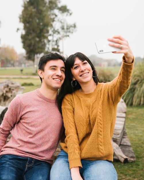 Sorrindo amigos tomando selfie no parque Foto gratuita