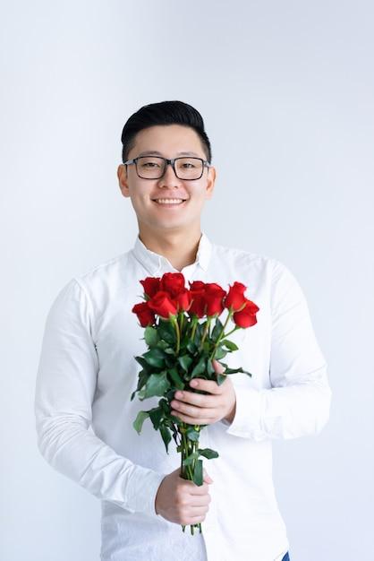Sorrindo, asian tripulam, segurando, grupo rosas Foto gratuita