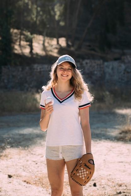 Sorrindo, ativo, femininas, com, basebol luva, ao ar livre Foto gratuita