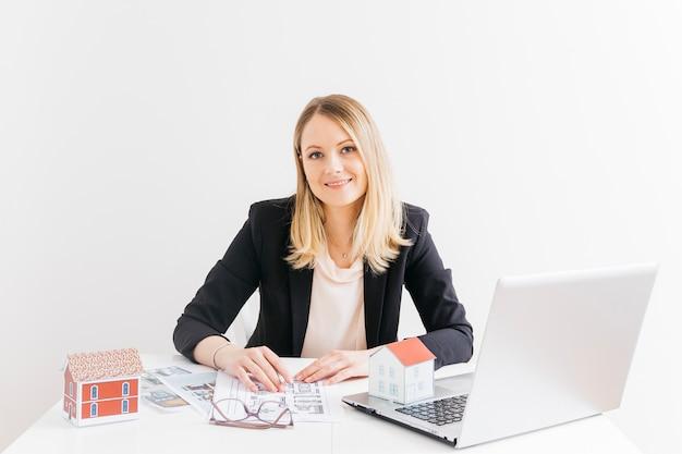Sorrindo atraente corretor de imóveis feminino sentado no escritório Foto gratuita