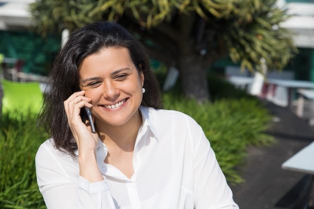 Sorrindo, atraente, mulher fala telefone móvel, ao ar livre Foto gratuita