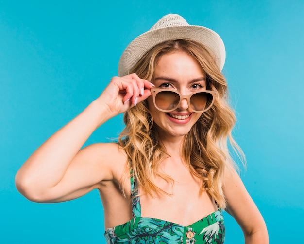 Sorrindo, atraente, mulher jovem, em, chapéu, e, óculos de sol Foto gratuita