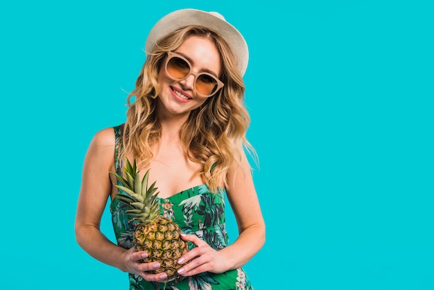 Sorrindo, atraente, mulher jovem, em, vestido, com, chapéu, e, óculos de sol, segurando, abacaxi fresco Foto gratuita