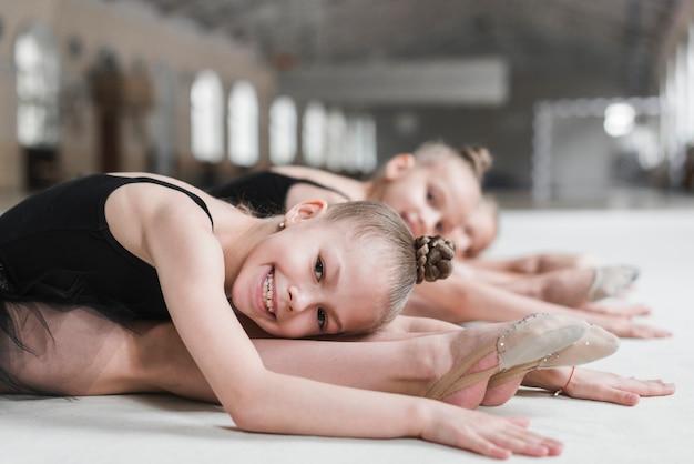 Sorrindo, bailarina, menina, posar, ligado, pista dança, com, dela, amigo Foto gratuita