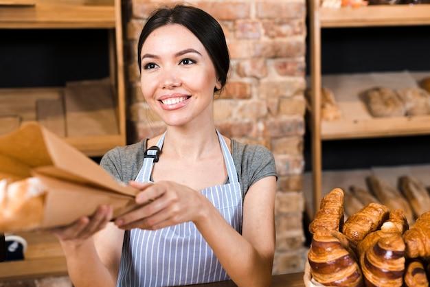 Sorrindo baker feminino dando pão embrulhado para o cliente na padaria Foto gratuita