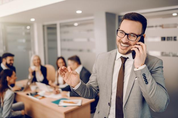 Sorrindo bonito empresário caucasiano com roupa formal, em pé na sala de reuniões e falando ao telefone. Foto Premium