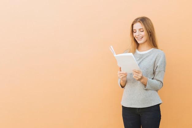 Sorrindo, bonito, mulher jovem, livro leitura, contra, colorido, fundo Foto gratuita
