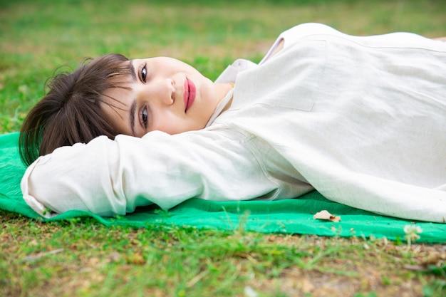 Sorrindo, bonito, mulher jovem, mentindo, e, relaxante, ligado, gramado Foto gratuita