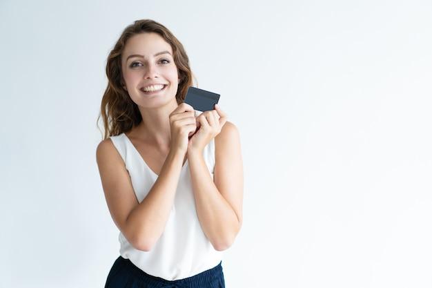 Sorrindo, bonito, mulher jovem, segurando, cartão plástico Foto gratuita