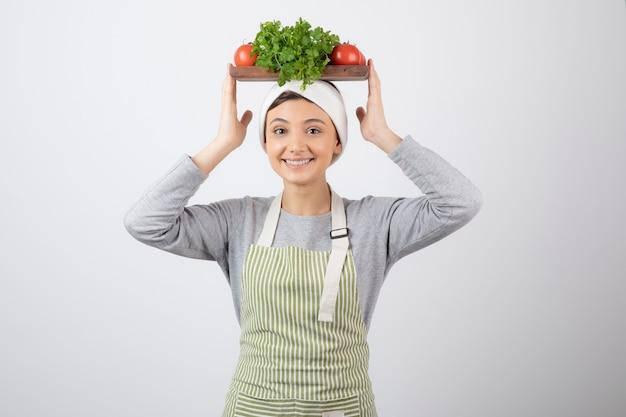 Sorrindo bonito mulher modelo segurando uma placa de madeira com legumes frescos na cabeça. Foto gratuita
