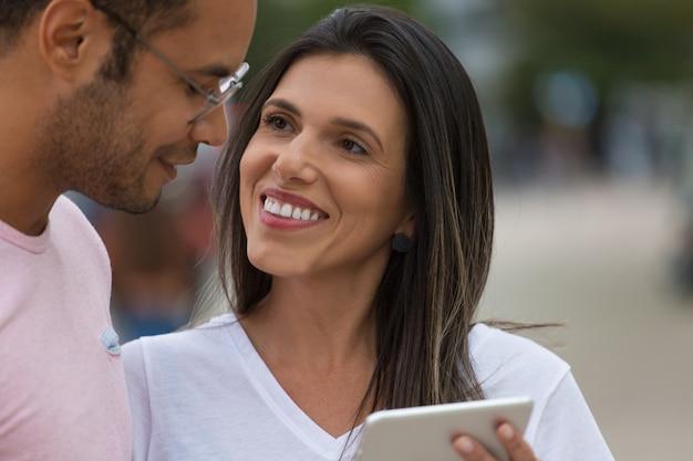 Sorrindo bons amigos com tablet na rua Foto gratuita