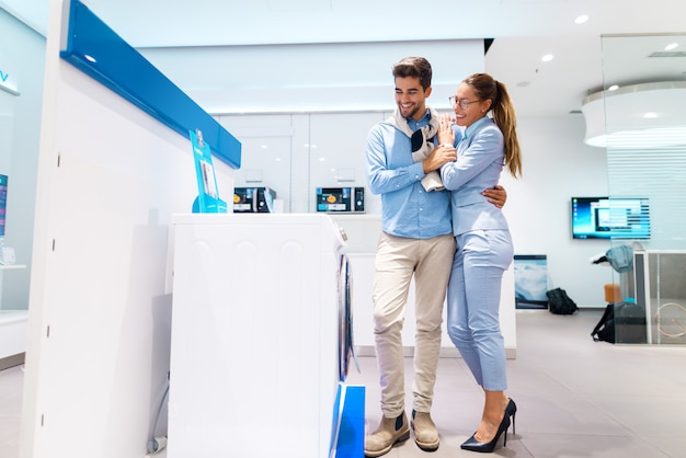 Sorrindo casal multicultural à procura de nova máquina de lavar. homem de pé enquanto mulher, apoiando-se nele. Foto Premium