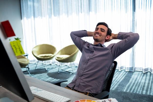 Sorrindo casual homem com as mãos atrás da mão, descansando na mesa Foto Premium