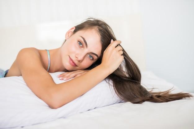 Sorrindo casual mulher morena deitada em sua cama no quarto brilhante Foto gratuita