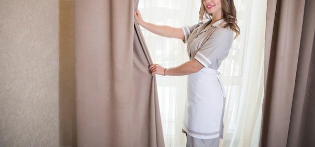 Sorrindo, chambermaid, abrindo, cortinas, em, a, sala Foto gratuita