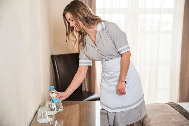 Sorrindo, chambermaid, colocar, a, garrafa água, ligado, tabela, em, a, quarto hotel Foto gratuita