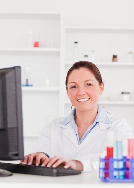 Sorrindo cientista digitando um relatório com o computador olhando a câmera Foto Premium