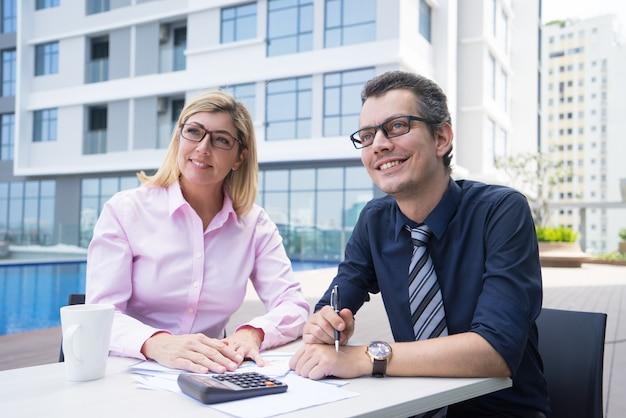 Sorrindo contadores ambiciosos, sentado à mesa com papéis e calculadora Foto gratuita