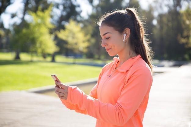 Sorrindo, desportivo, mulher, usando, smartphone, parque Foto gratuita