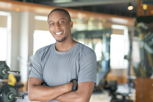 Sorrindo desportivo negro em pé com os braços cruzados Foto gratuita