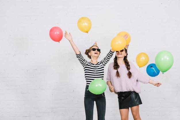 Sorrindo, dois, femininas, amigos, ficar, contra, branca, parede, tocando, com, balões coloridos Foto gratuita