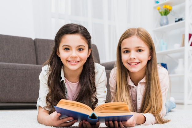 Sorrindo, dois, femininas, amigos, mentindo tapete, segurando livro, em, mão Foto gratuita