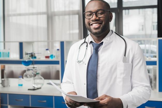 Sorrindo doutor negro com papéis Foto gratuita